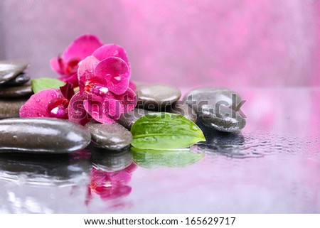Composition with beautiful blooming orchid with water drops and spa stones, on light color background - stock photo