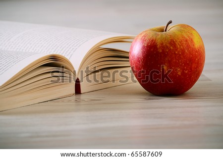 Composition with book and apple on the wooden table - stock photo