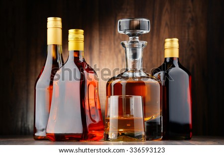 Composition with bottles of assorted alcoholic beverages and glass of whisky - stock photo