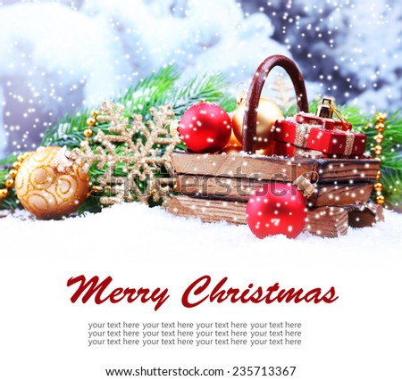 Composition with Christmas decorations in basket, fir tree on winter background - stock photo