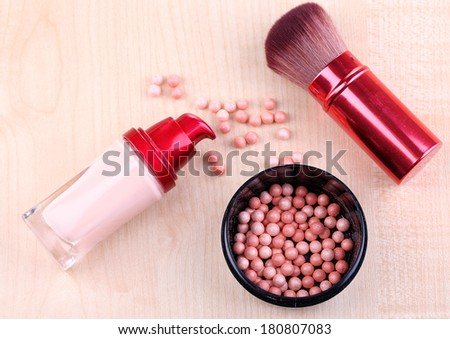 Composition with concealer, powder balls and brush on wooden background - stock photo