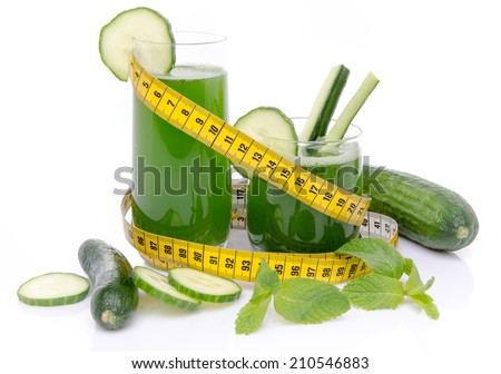 Composition with cucumber juice, fresh cucumbers and a tape measure, isolated on white - stock photo