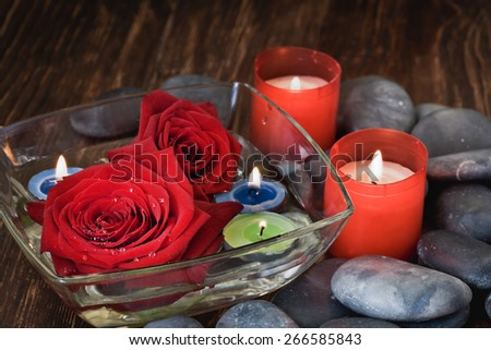 Composition with flowers, candles and stones - stock photo
