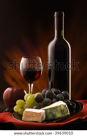 composition with glass and bottle of red wine with various types of cheese and grapes - stock photo