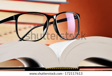 Composition with glasses and books on the table - stock photo