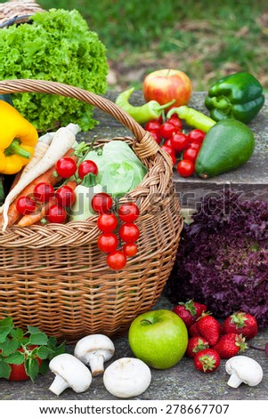 Composition with raw vegetables and wicker basket in the garden - stock photo