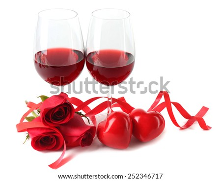 Composition with red wine in glasses, red roses, ribbon and decorative hearts isolated on white - stock photo