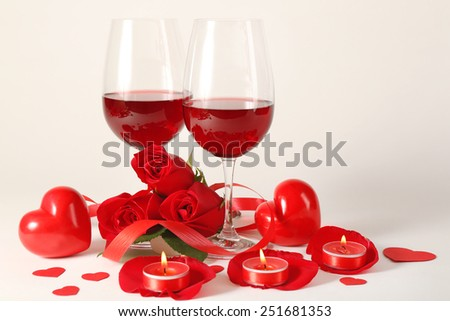 Composition with red wine in glasses, red roses, ribbon and decorative hearts on light background - stock photo
