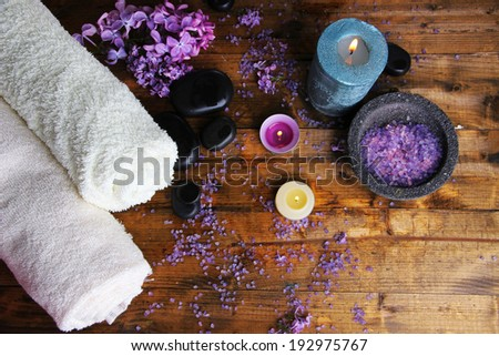 Composition with spa treatment, towels and lilac flowers, on wooden background - stock photo