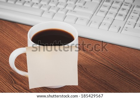 Composition with sticker on the cup and keyboard on wooden desk - stock photo