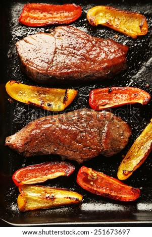Composition with tasty roasted meat and sliced pepper on pan, tomatoes and rosemary sprigs close-up - stock photo