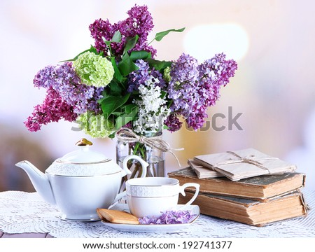 Composition with teapot,  mug and beautiful spring flowers in vase, on wooden table, on bright background - stock photo