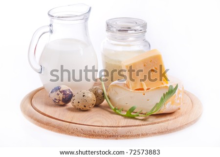 Composition with tow kind of cheese, quail's eggs, mayonnaise and jug of milk on the wooden desk - stock photo