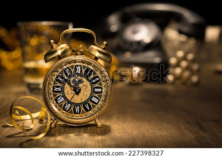 Composition with vintage alarm clock showing five to midnight and an old phone. Happy New Year 2015! - stock photo