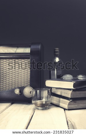 Composition with vintage items on table Vintage radio, books, glasses and whiskey on wooden surface. Edited image with vintage effect - stock photo