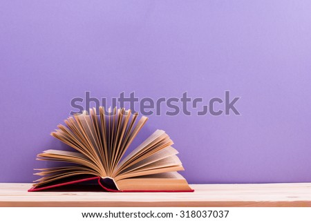 Composition with vintage old hardback books, diary, fanned pages on wooden deck table and purple background. Books stacking. Back to school. Copy Space. Education background - stock photo
