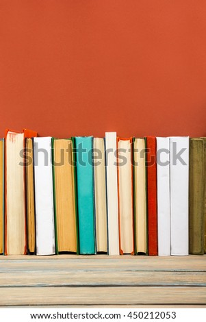 Composition with vintage old hardback books, diary on wooden deck table and red background. Books stacking. Back to school. Copy Space. Education background. - stock photo