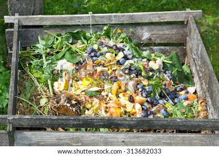 Compost bin in the garden. Composting pile of rotting kitchen fruits and vegetable scraps - stock photo