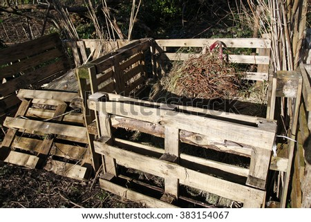 Compost bins made from old pallets in an allotment - stock photo