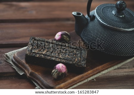 Compressed herbal tea and tetsubin teapot, wooden background - stock photo