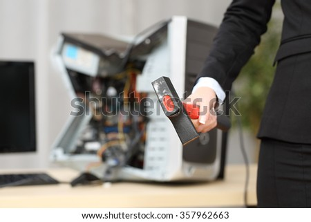 Computer absolutely destroyed by a hot-tempered businesswoman hand holding a hammer - stock photo