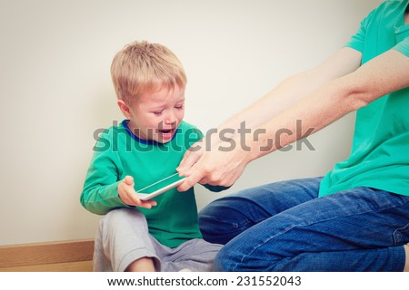 computer addiction, parent taking out touch pad from child - stock photo