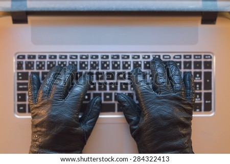Computer crime metaphor, hand in black gloves on a computer.  - stock photo
