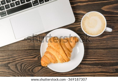 Computer, Cup Coffee and Croissant on brown wood table - stock photo