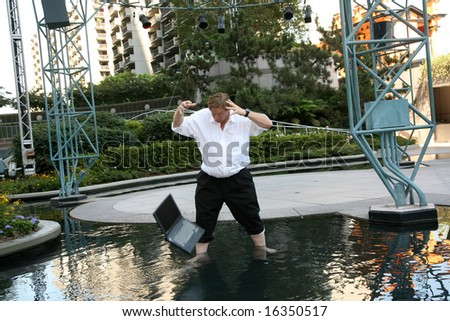 Computer damage concepts a business man is upset as he realizes that he just dropped his laptop in a pool of water - stock photo