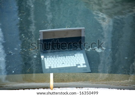 Computer damage concepts Laptop computer submerged in a pool of water - stock photo