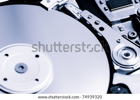 Computer hard disk inside close-up, lightly blue toned - stock photo