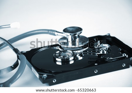 Computer hard drive and a stethoscope. Symbol of a secure computer work - stock photo
