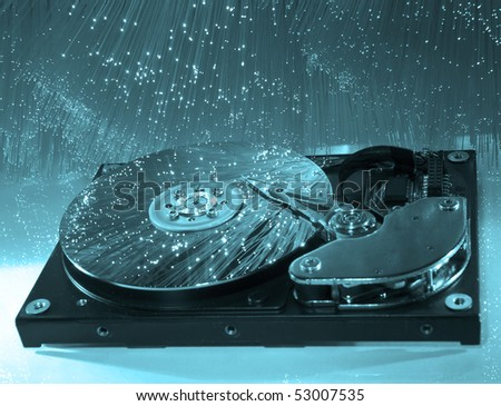 computer harddisk and heads on technology fiber optics background - stock photo