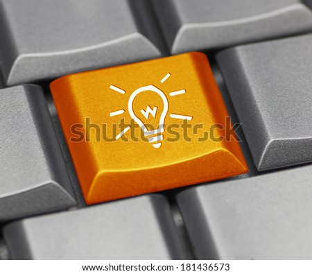 Computer key orange - light bulb - stock photo