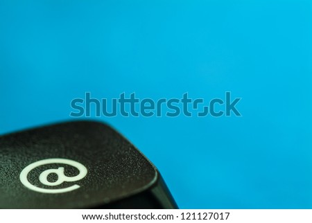 Computer key with e-mail icon against a blue background - stock photo