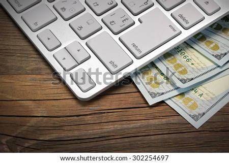 Computer Keyboard  And Dollar Cash On The Rough Wood Background. E-commerce Or Freelance Work Concept - stock photo