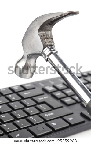 Computer keyboard and hammer - stock photo