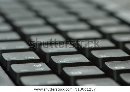 Computer keyboard.  Close up of mostly blurred bands of keys on an angle. - stock photo