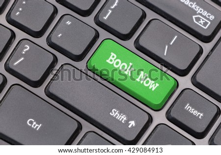 "Computer keyboard closeup with ""Book Now"" text on green enter key - stock photo"