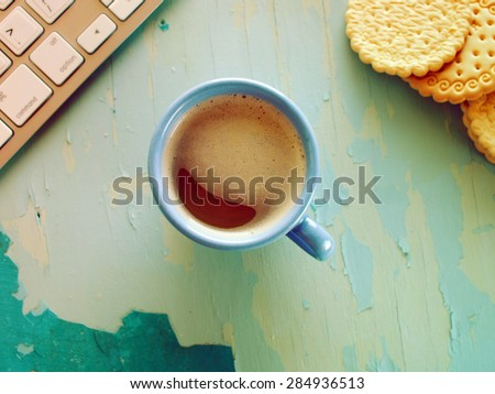 Computer keyboard, cup of coffee and biscuits on blue painted weathering table. Grunge style - stock photo