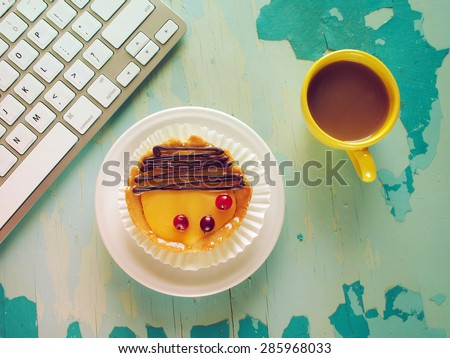 Computer keyboard, cup of coffee and  cake on blue painted weathering table. Grunge style - stock photo