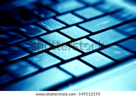 Computer keyboard in blue light. Small depth of field.  - stock photo