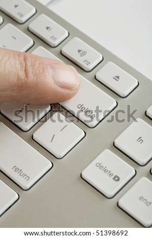 Computer keyboard with mans finger on delete key - stock photo