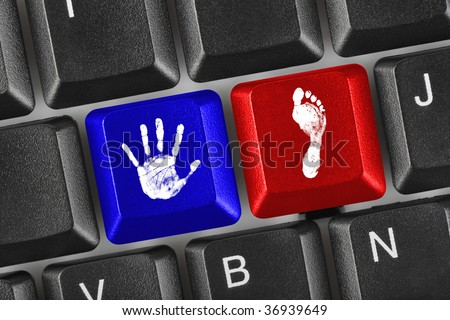 Computer keyboard with printout of hand and foot keys - stock photo
