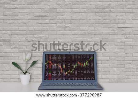 computer laptop, white tulip flower vase with white brick wall background : interior and busine?s concept - stock photo