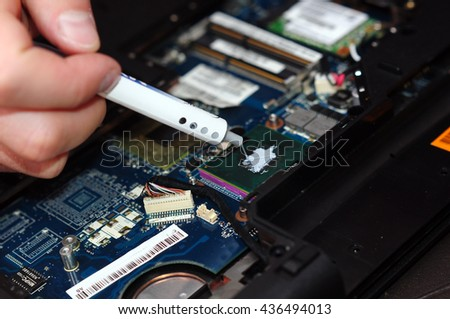 Computer literacy repair men hands, examines laptop clean thermal paste Horizontal view of cleaning processor and fan - stock photo