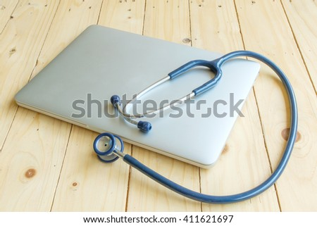 Computer,Medical stethoscope and Birth control pill on wood table. - stock photo