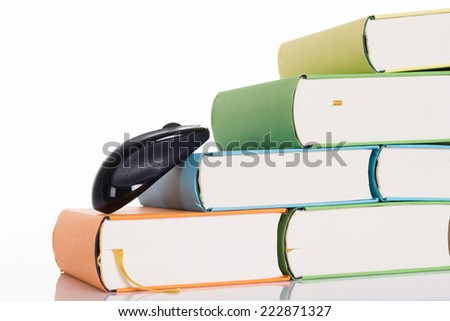Computer mouse climbing books. Isolated on white - stock photo