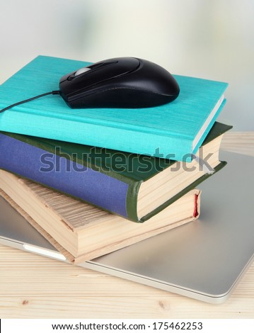 Computer mouse on books and notebook on wooden table on room background - stock photo