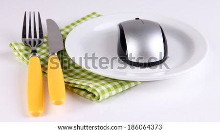 Computer mouse on plate with fork and knife isolated on white - stock photo